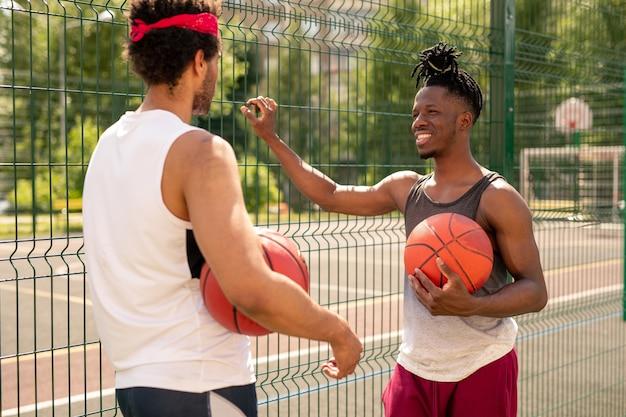 Dois jovens jogadores de basquete multiculturais interagindo após o jogo enquanto estavam perto da cerca