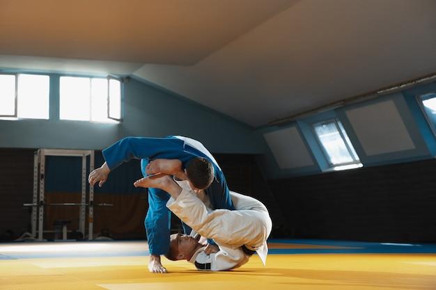 Dois jovens judocas de quimono treinando artes marciais no ginásio com expressão em ação e movimento