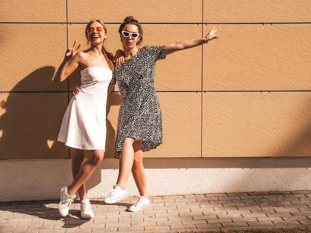 Dois jovens lindas garotas hipster sorridente no verão na moda vestidos.