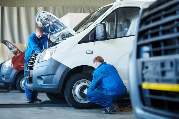 Dois jovens mecânicos de uniforme fazendo revisão técnica de carro ou consertando motor e rodas em centro de serviços