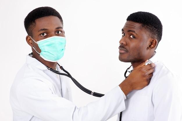 Dois jovens médicos africanos em um branco isolado com um estetoscópio. um deles com máscara.