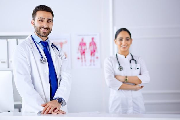 Dois jovens médicos árabes sorridentes em pé na sala de consulta no hospital