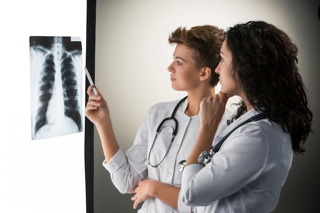 Dois jovens médicos atraentes olhando os resultados de raios-x