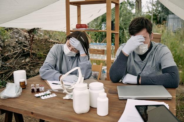 Dois jovens médicos exaustos em trajes de trabalho de proteção sentados à mesa