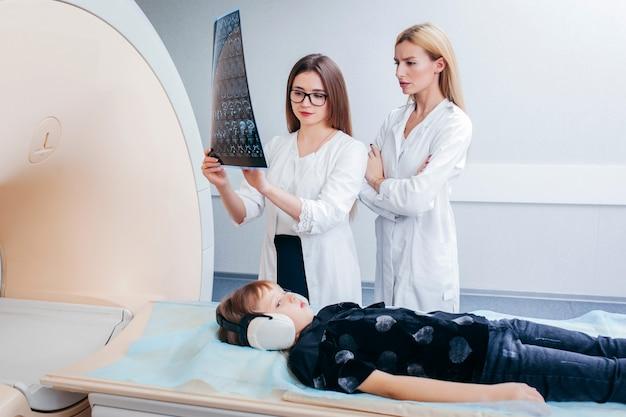 Dois jovens médicos femininos verificando uma criança na sala de ressonância magnética