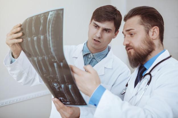 Dois jovens médicos masculinos discutindo varredura de raios-x