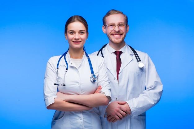 Dois jovens médicos, um cara e uma garota, em vestes brancas, sorriem sobre um fundo azul.