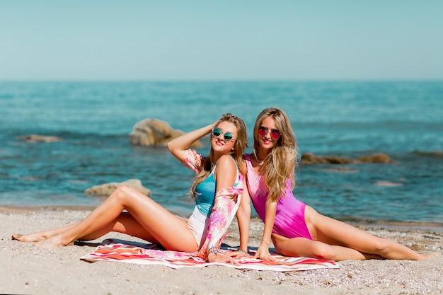 Dois jovens melhores amigos sentados na praia tropical e curtindo as férias de verão.