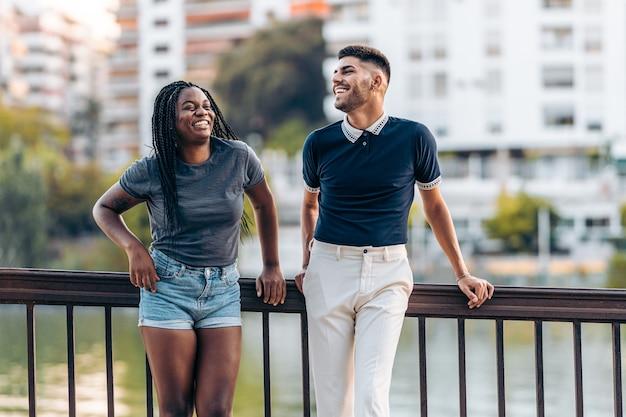 Dois jovens modernos de diferentes etnias rindo em pé na rua durante o verão