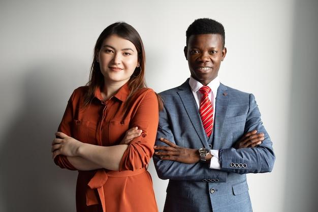 Dois jovens, mulher asiática e homem africano em trança