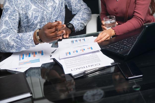 Dois jovens negros discutem seus negócios usando diagramas sentado à mesa no escritório