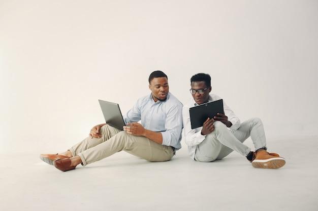 Dois jovens negros trabalhando juntos e usam o laptop