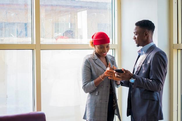 Dois jovens parceiros de negócios africanos discutindo sobre o que viram em seu celular.