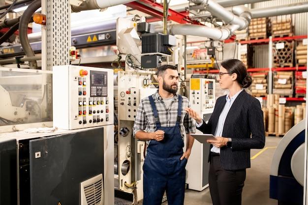 Dois jovens parceiros de negócios discutindo métodos de trabalho de produção industrial ou processamento de matérias-primas