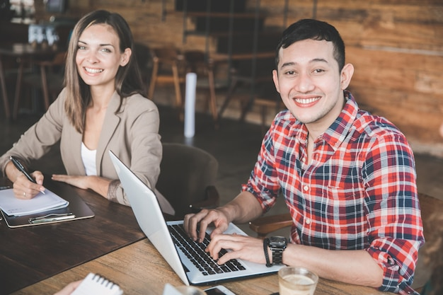 Dois jovens parceiros sentados juntos em uma cafeteria fazendo reunião