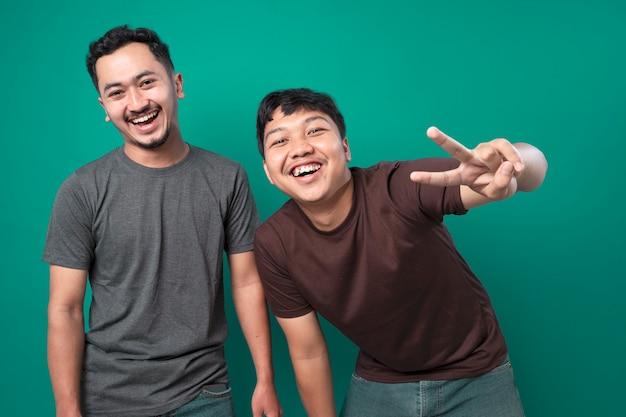 Dois jovens rindo e torcendo com seu amigo contra um fundo azul