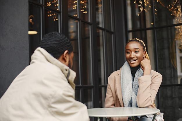 Dois jovens sentados do lado de fora. casal africano, aproveitando o tempo que passa um com o outro.