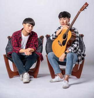 Dois jovens sentados em uma cadeira segurando um violão