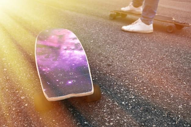 Dois jovens skatistas se apresentando com skate ao pôr do sol no parque urbano da cidade - jovens se divertindo com longboards - esporte radical e conceito de estilo de vida jovem - foco suave no pé direito do homem