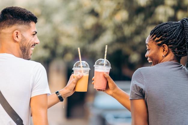 Dois jovens sorridentes de diferentes etnias brindando com um shake na rua