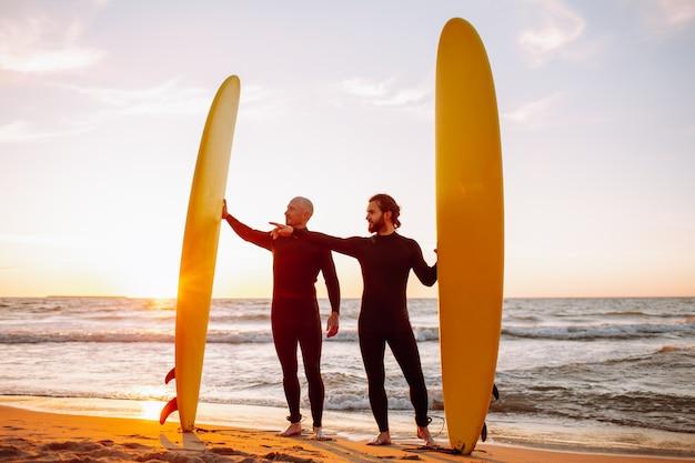 Dois jovens surfistas em roupa de mergulho preta com longboards de surf amarelo em uma costa do oceano no oceano por do sol