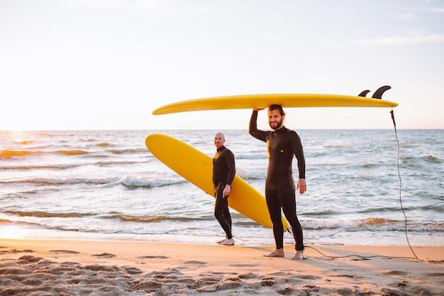 Dois jovens surfistas em roupa de mergulho preta com longboards de surf amarelo na costa do oceano ao pôr do sol. acampamento de aventura de esportes aquáticos e natação extrema nas férias de verão.