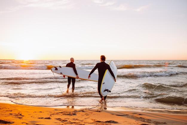 Dois jovens surfistas masculinos em roupas de mergulho pretas com longboards indo para a água no oceano por do sol