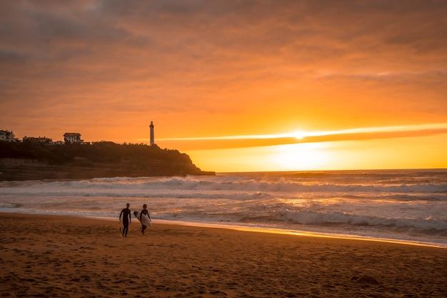 Dois jovens surfistas na praia da casinha do amor. biarritz, aquitânia. frança
