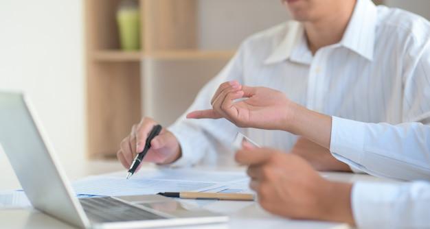 Dois jovens trocaram idéias com uma caneta no gráfico e um laptop.
