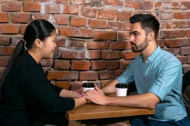 Dois jovens, um garoto e uma garota conversando de mãos dadas em um café no fundo de uma parede de tijolos ásperos
