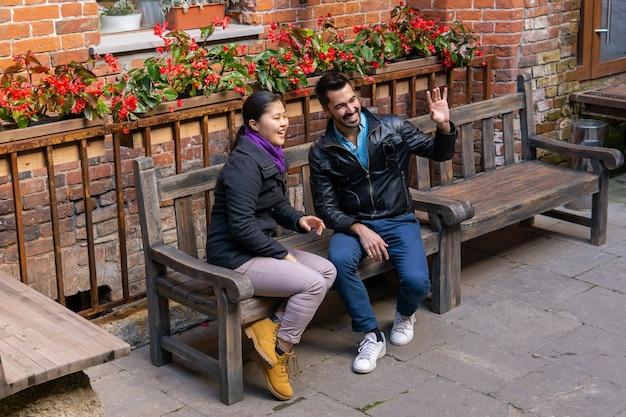 Dois jovens, um rapaz e uma rapariga sentados num banco ao ar livre, cumprimentam alguém