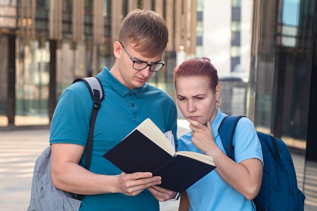 Dois jovens universitários ou universitários com mochilas. garoto e garota estão olhando para um livro, um livro didático