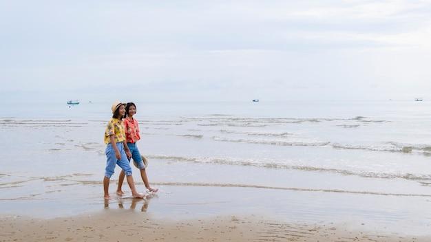 Dois jovens usam chapéu e jeans caminhando na bela praia.