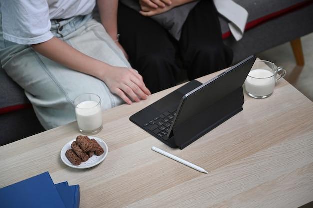 Dois jovens usando computador tablet e sentados juntos no sofá em casa.
