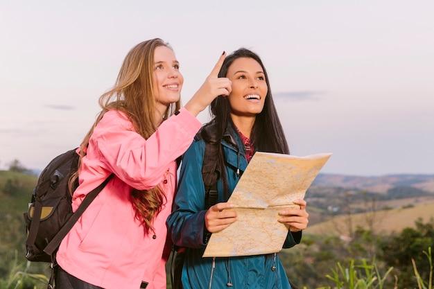 Dois jovens viajantes à procura de seu próximo destino com um mapa