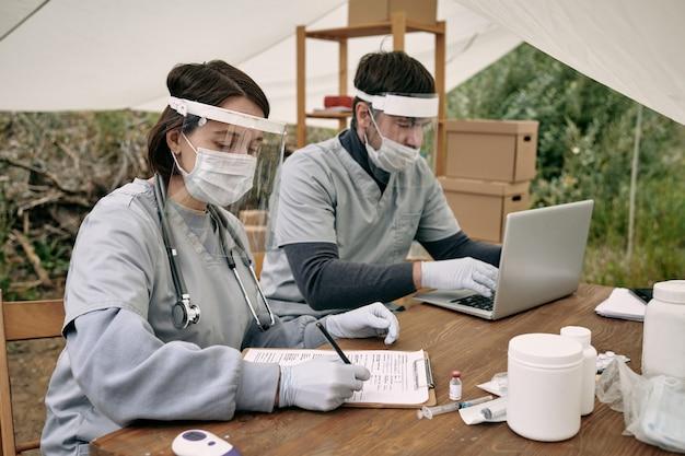 Dois jovens voluntários em uniforme médico trabalhando em campo de refugiados
