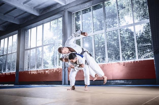Dois judocas demonstrando habilidade técnica enquanto praticavam artes marciais em um clube de luta. os dois são homens uniformizados. luta, caratê, treinamento, artes, atleta, conceito de competição