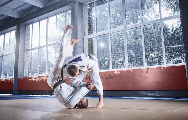 Dois judocas demonstrando habilidade técnica praticando artes marciais em um clube de luta
