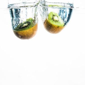 Dois kiwi metade espirrando na água sobre o fundo branco