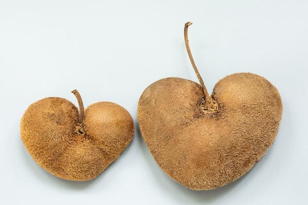Dois kiwis feios em forma de coração em uma superfície cinza.