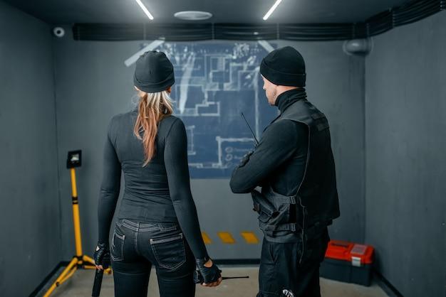 Dois ladrões trabalhando em um plano para roubar o cofre
