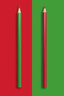 Dois lápis de verde e vermelho em um vermelho e verde