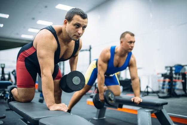 Dois levantadores de peso fazendo exercícios com halteres