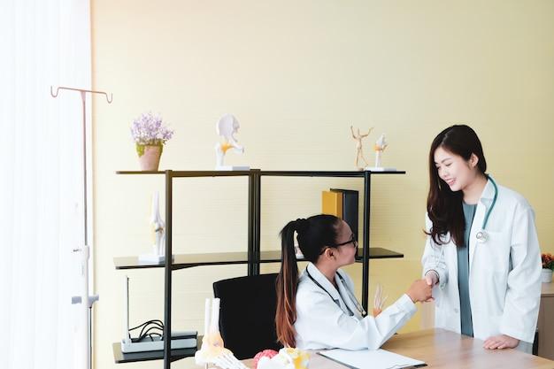 Dois lindos médicos se levantam para aplaudir os pacientes no escritório.