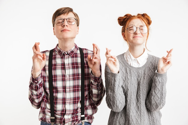 Dois lindos nerds de escola segurando dedos cruzados