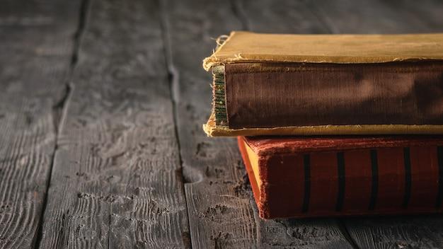 Dois livros antigos em uma mesa de madeira preta. literatura do passado.