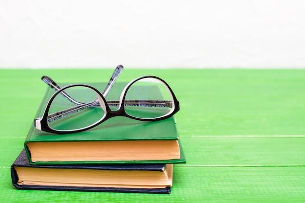 Dois livros de capa dura e copos em uma mesa de madeira verde. copie o espaço