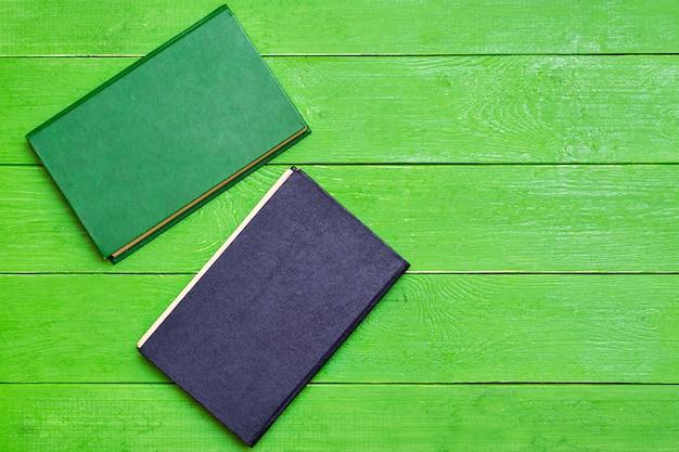 Dois livros de capa dura sobre um fundo verde de madeira. vista do topo