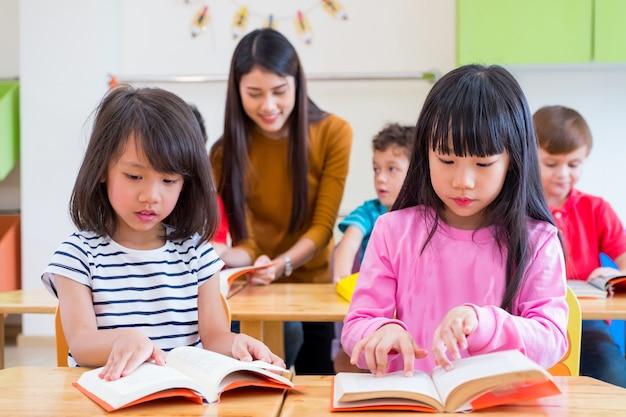 Dois livros de leitura de garotos asiáticos na sala de aula e enquanto professores ensinam amigos ao lado deles