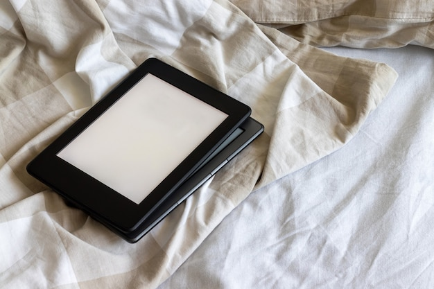 Dois livros eletrônicos modernos com telas vazias em branco em uma cama branca e bege. comprimidos de maquete um em cima do outro na cama